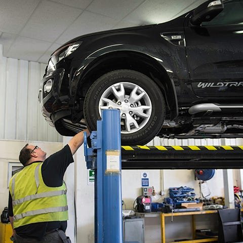 Vehicle on Lift with Fitter Looking Underneath